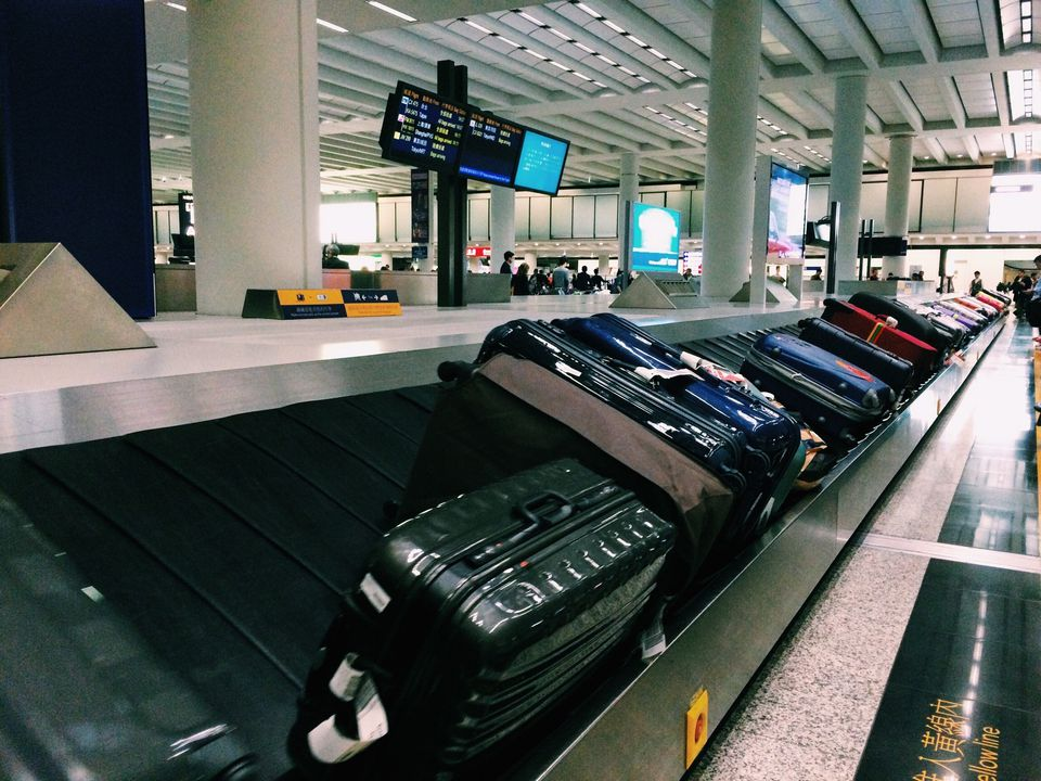 Row Of Suitcases On Conveyor Belt At Airport