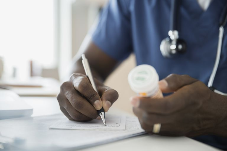 Close up of doctor with bottle writing prescription