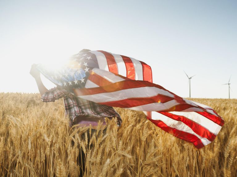 girl flying American flag in field