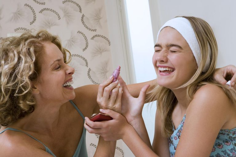 Mother helping daughter (13-15) with make-up, laughing