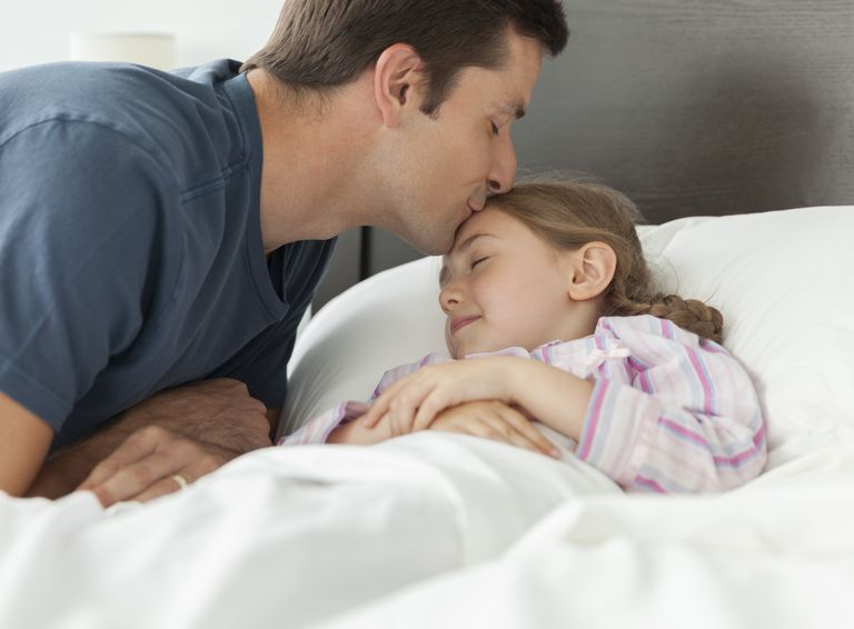 father kissing daughter in bed