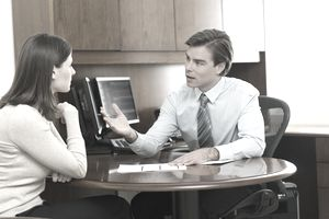 Man and woman talking at business table