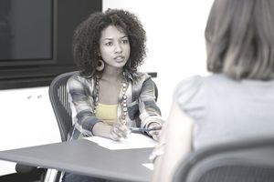 women talking across office table