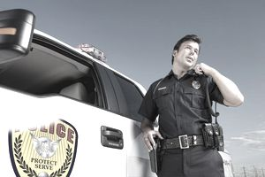 A police officer speaking into a shoulder harnessed two-way radio