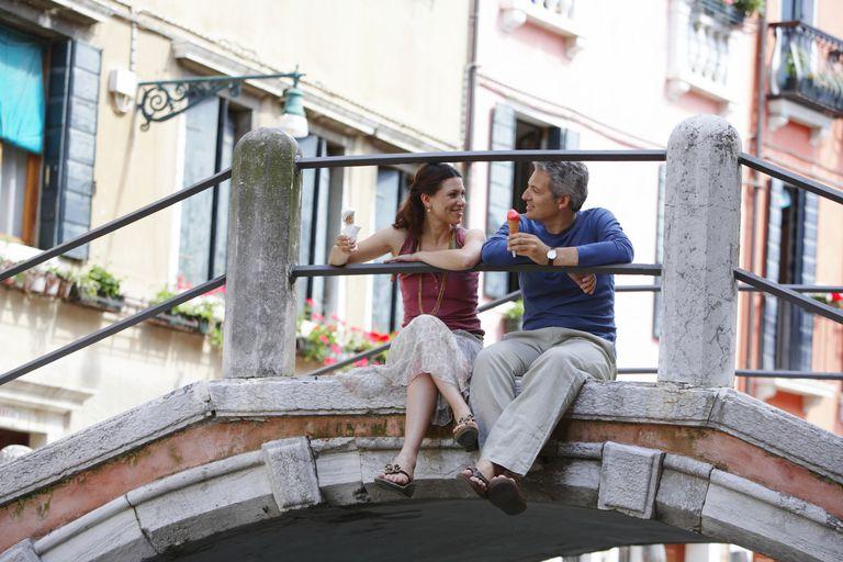 Italy, Venice, couple sitting on bridge holding ice cream cones