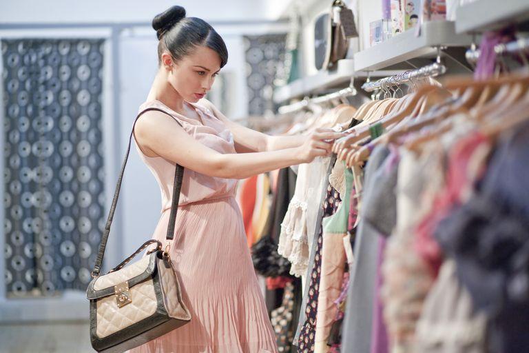 Woman sifting through clothing racks at store