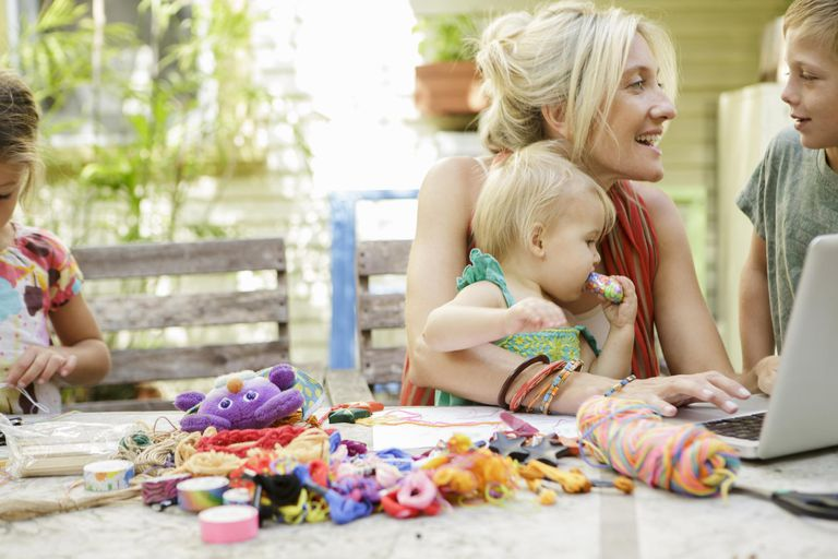 Mother and children at garden table with laptop and crafts