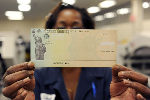 Social Security worker holding up a benefit check