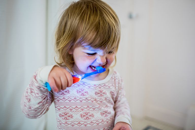Toddler brushing teeth with a light up toothbrush