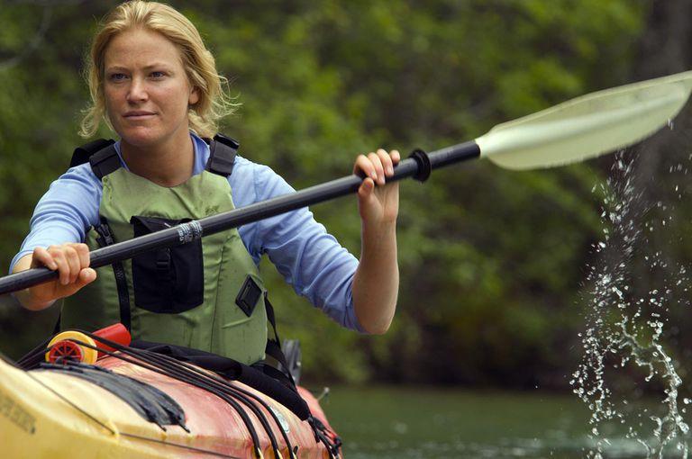 Woman sea kayaking on lush lake.