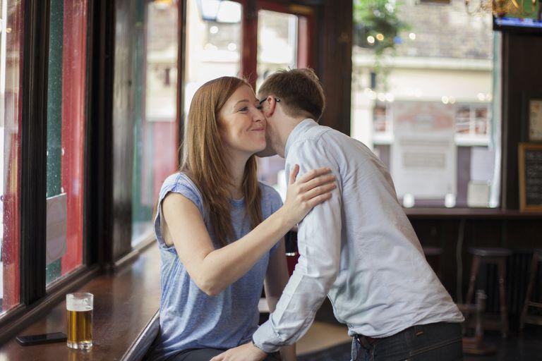 Woman greeting man in bar