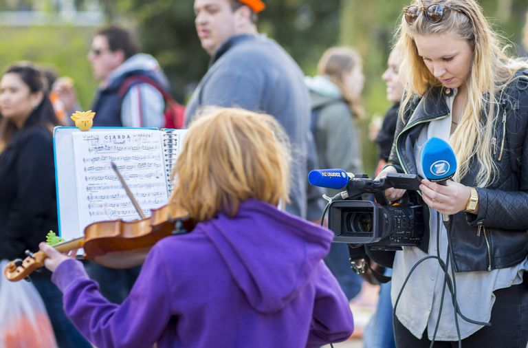 A photo of a camerawoman recording video of a child playing a violin