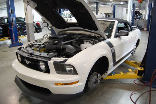 A Mustang in a shop with the hood up.