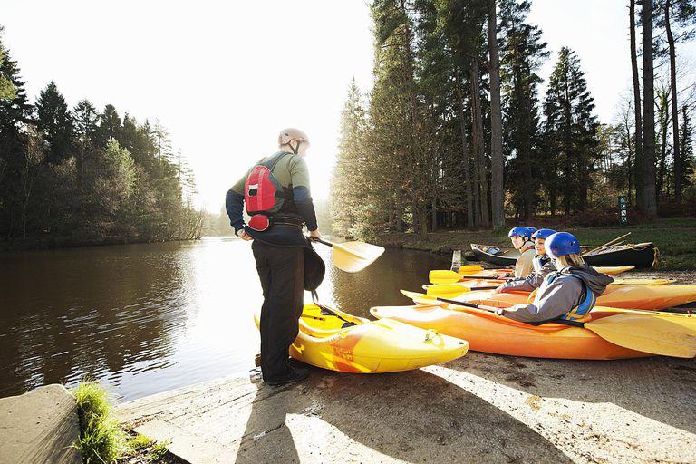 Kayaks lined up at edge of lake