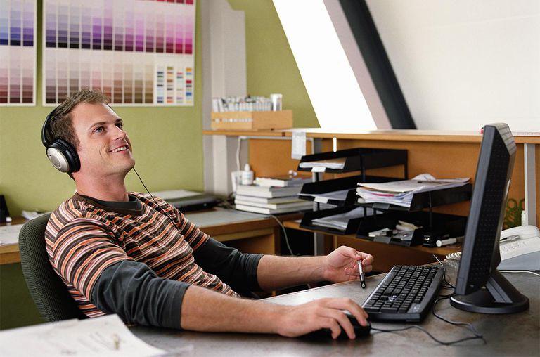 Man wearing headphones sitting at computer, smiling