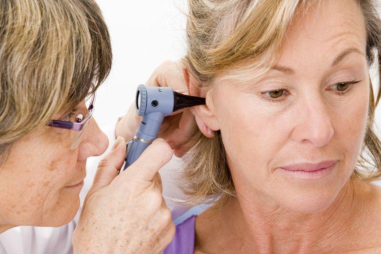 Doctor examining a woman's ear.