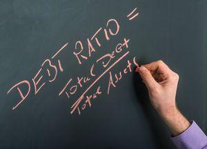 debt ratio on blackboard with hand