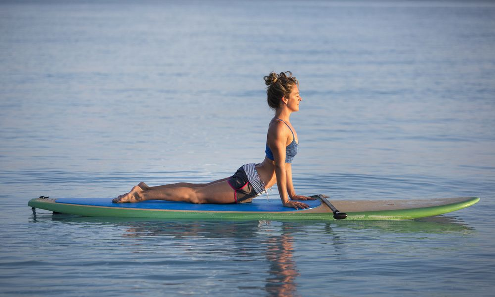 Woman doing yoga on stand-up paddle board
