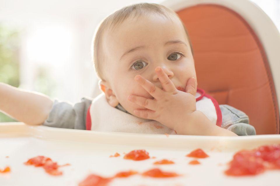 Baby boy eating gelatin dessert in high chair