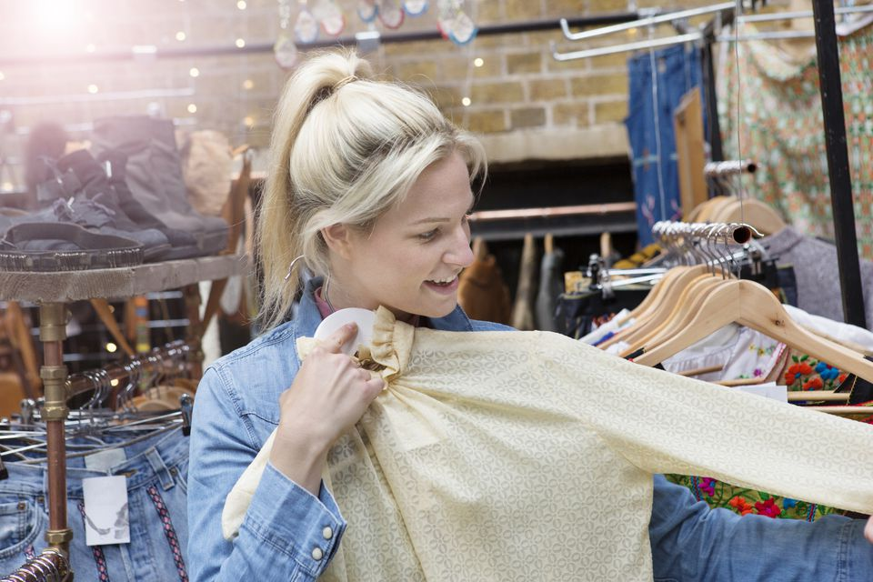 Woman looking at shirt in vintage market stall.