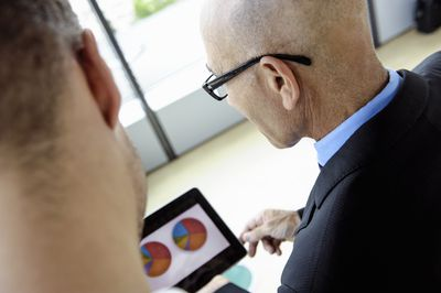 Man looking at 2 pie charts of his stock to bond mix.