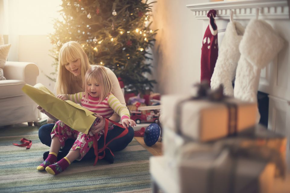 USA, New Jersey, Mother and daughter (4-5) opening christmas presents