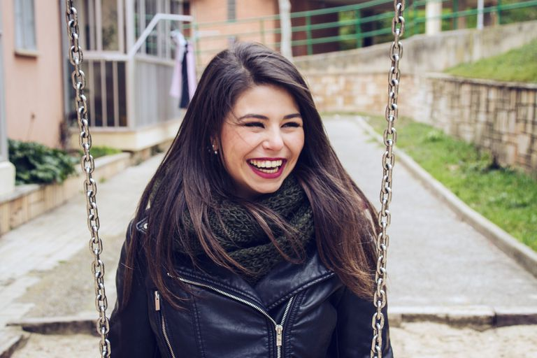 Smiling woman on a swing.