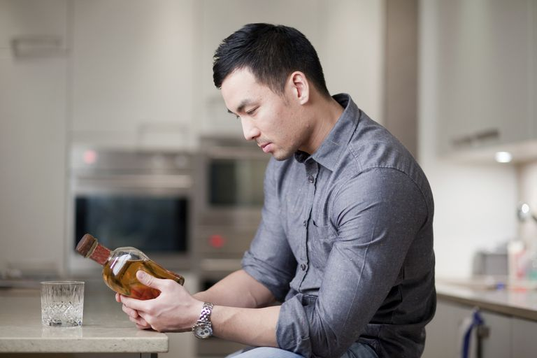 man looking at whiskey bottle in kitchen