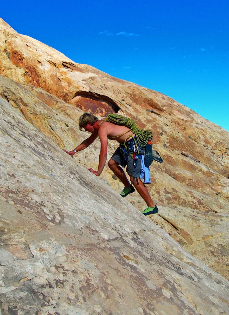 CJ Sidebottom scrambles up a sandstone slab at the San Rafael Swell, Utah.