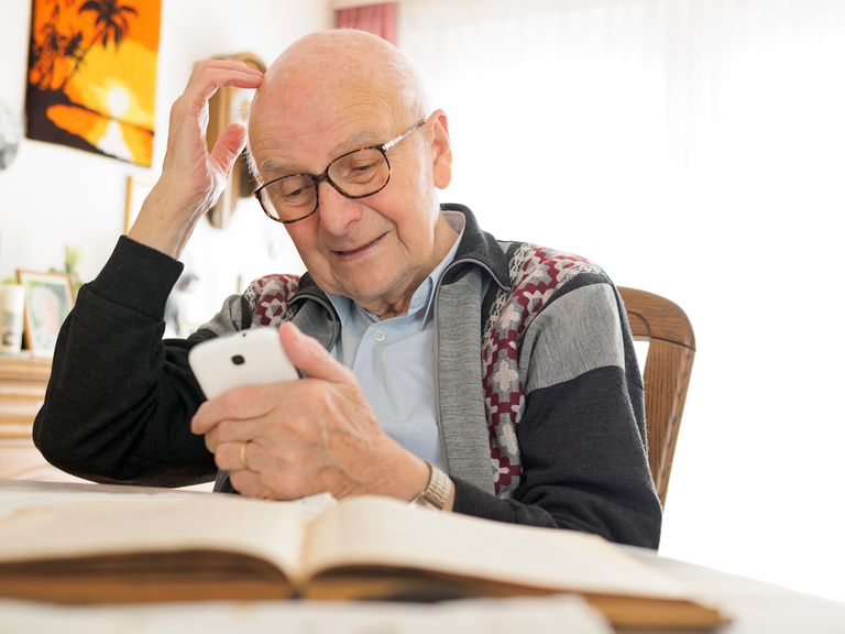 Old man sitting at table using cell phone.