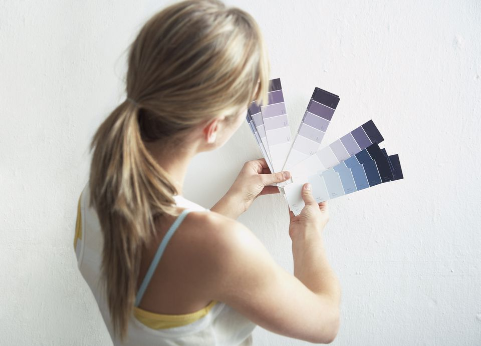 Woman holding paint swatches up to the wall