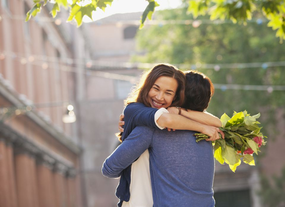 Smiling woman with flowers hugging man