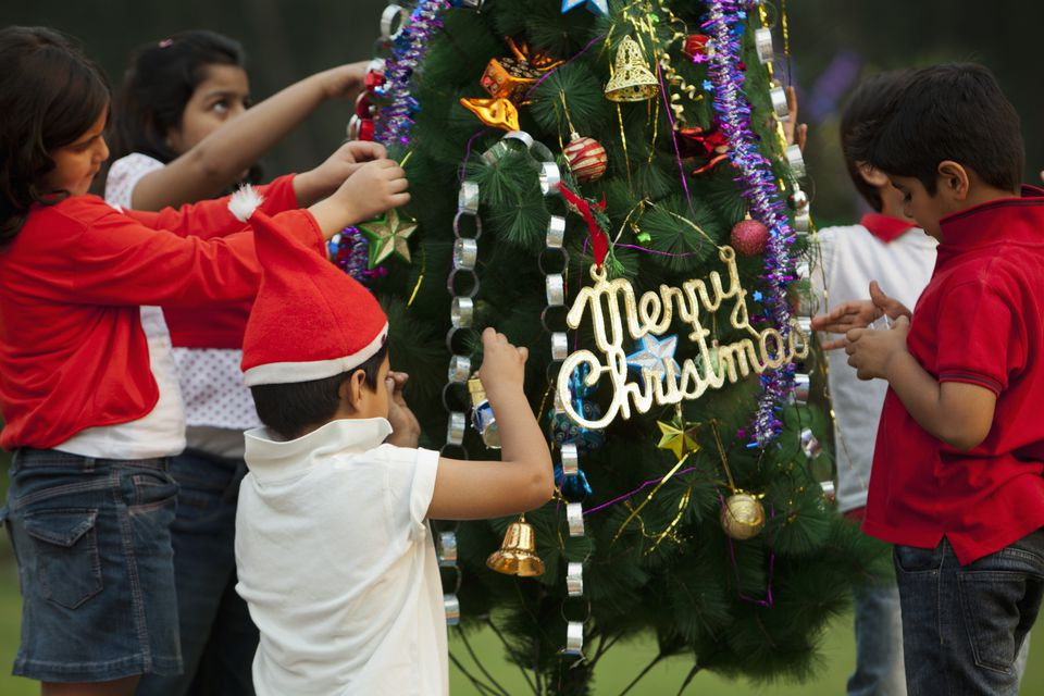Children decorating Christmas tree in India.