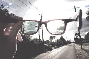 Young Man Holding Eyeglasses