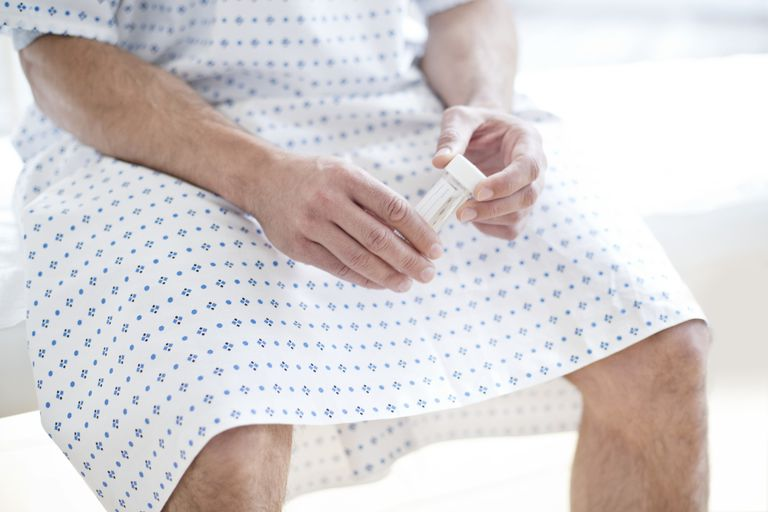 man in hospital gown holding urine sample