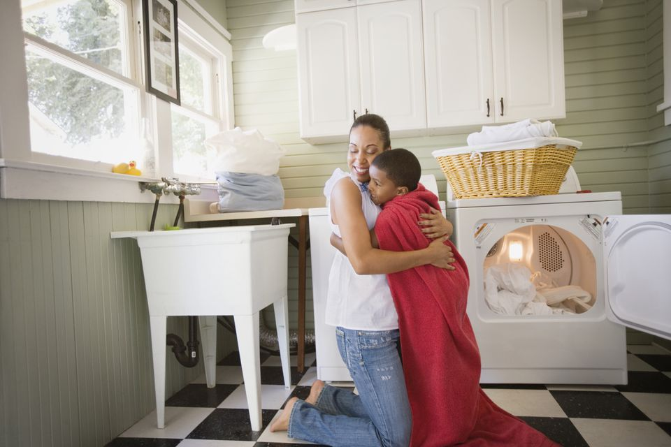 Mixed race mother hugging son wearing towel