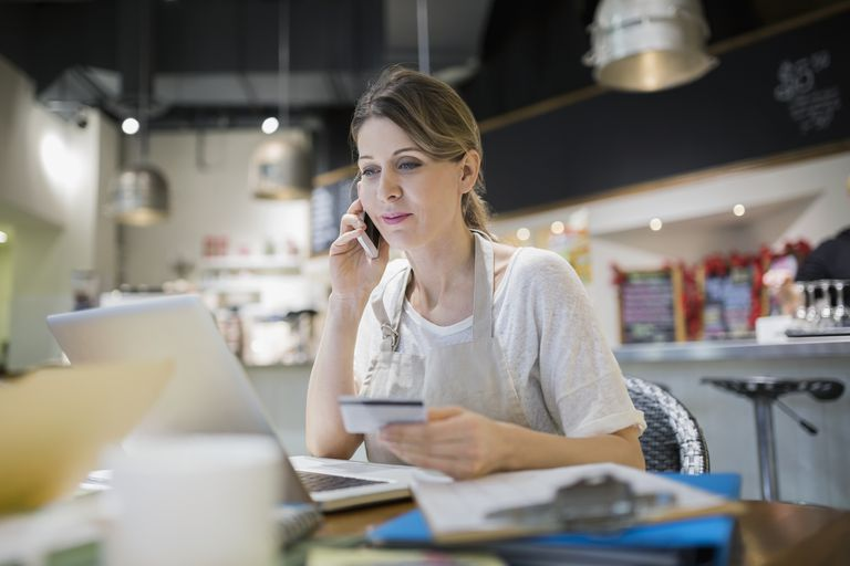 Business owner paying bills at laptop in cafe