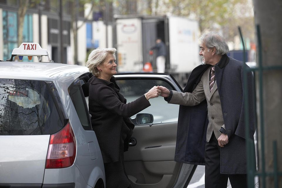 Mature man assisting senior woman out of taxi, side view