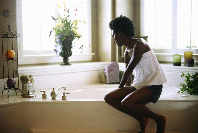 Young woman sitting on edge of bathtub.