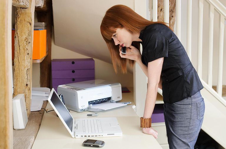 Young business woman using mobile in home office.
