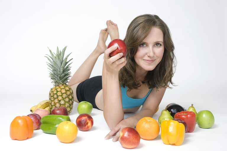 Woman surrounded by fruits and vegetables