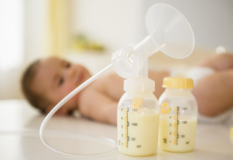Breast pump shield with plastic bottles containing breast milk and a baby in the background