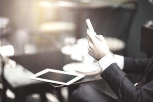 Businessman texting at a sidewalk cafe