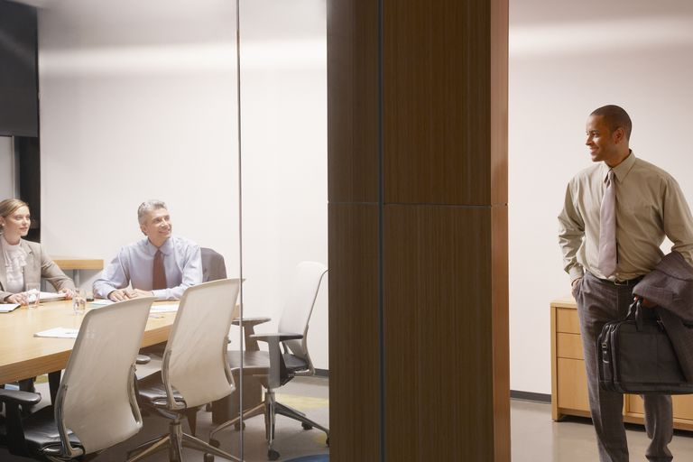 Two businesspeople in boardroom watching businessman leave