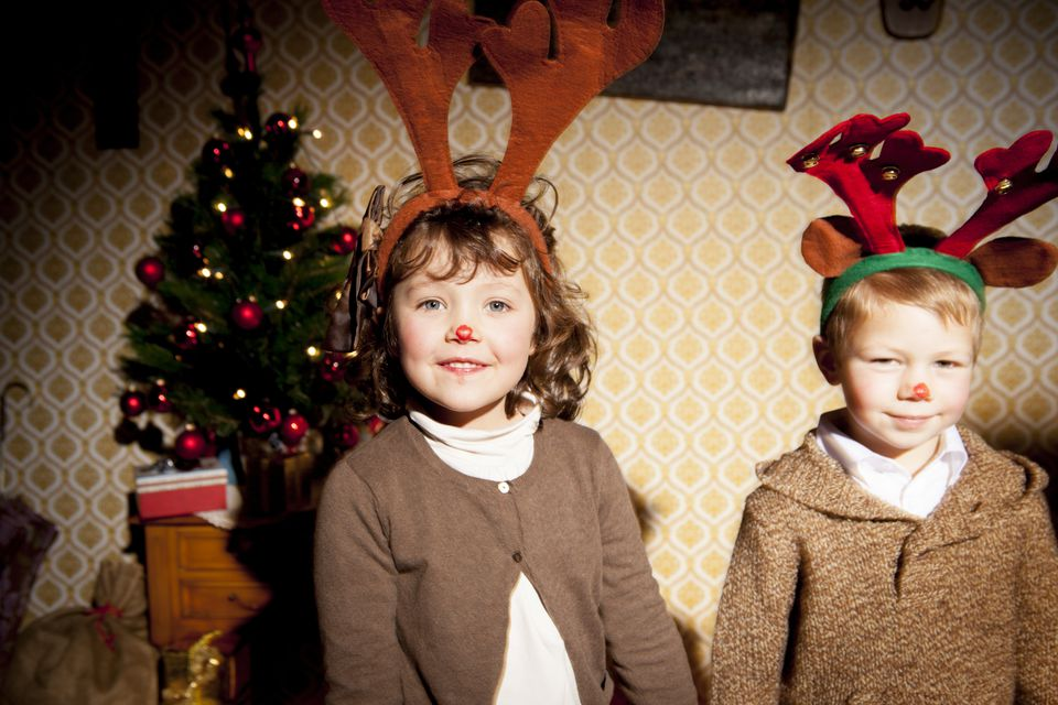 Boy and girl (4-7) wearing antlers during Christmas