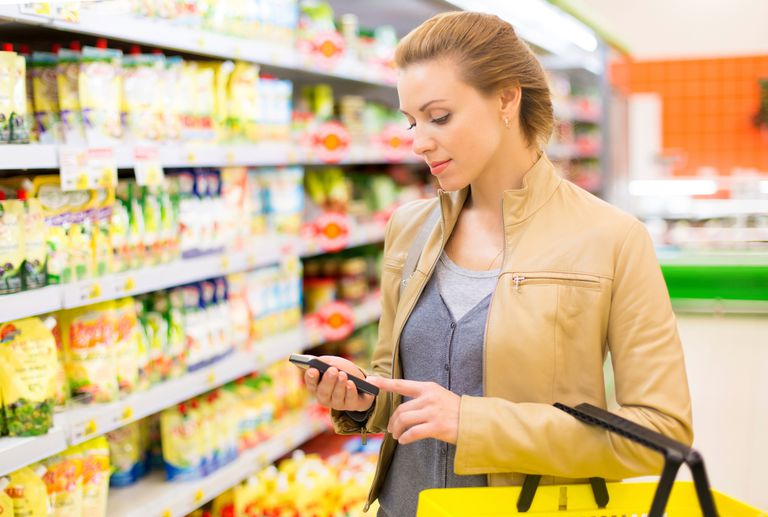 woman using smartphone at grocery store