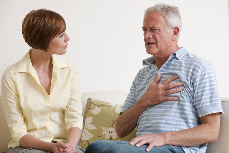 man with chest pain and woman sitting on couch