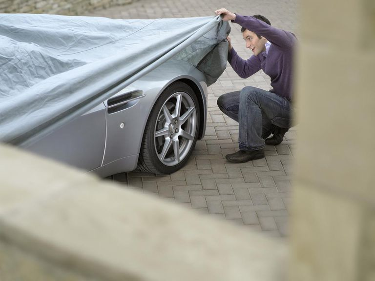 Young man looking under protective sheet on car, smiling