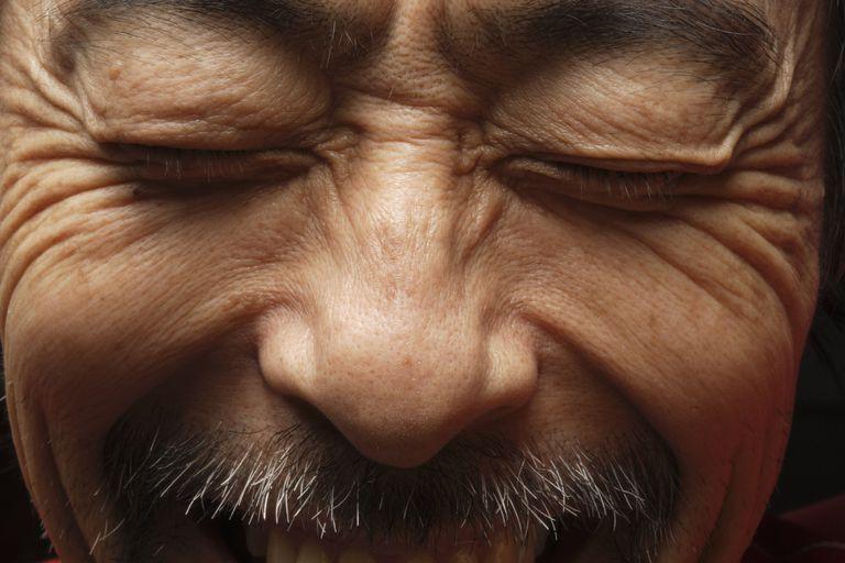 Eyes closed Asian man smiling