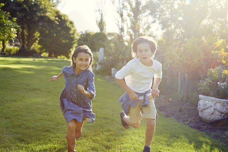 Two young children running in garden